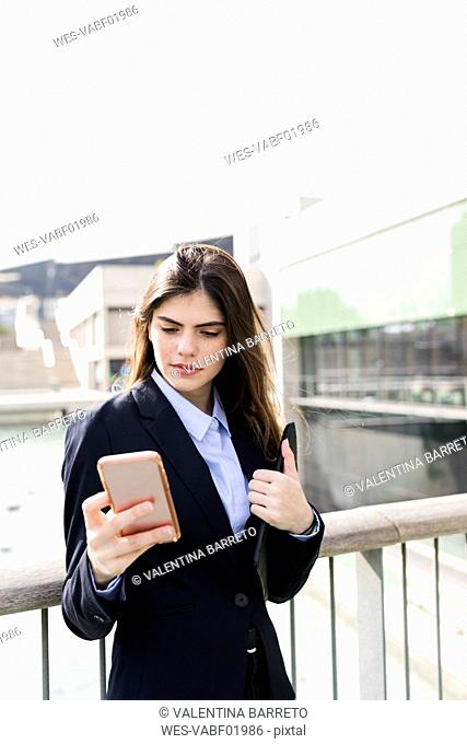 Young businesswoman using cell phone in the city