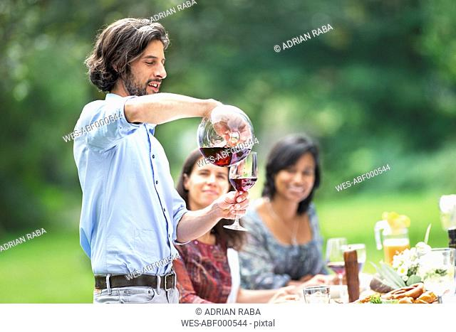 Man pouring red wine on a garden party