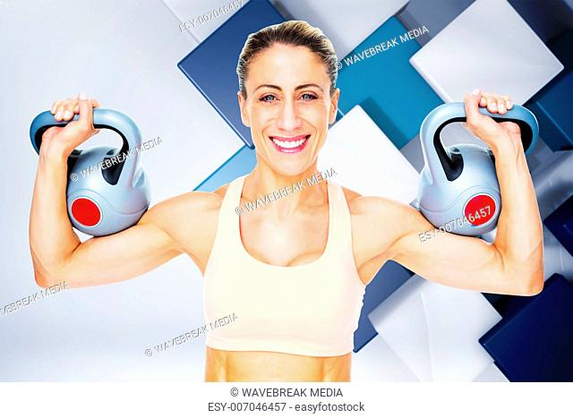 Composite image of happy female crossfitter lifting kettlebells looking at camera