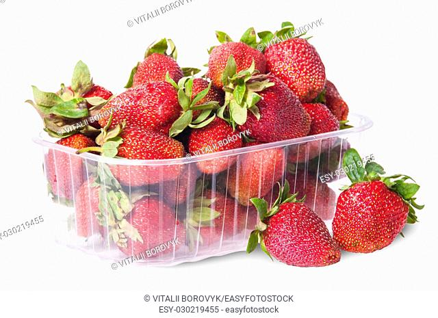 Freshly strawberries in a plastic tray and two near rotated isolated on white background