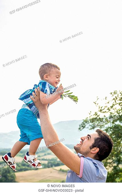 Father Lifting Son in Air