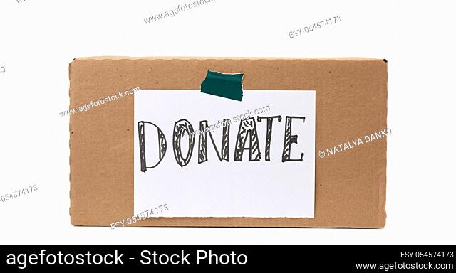 brown cardboard box with a pasted white sheet and the inscription donate on a white background, help concept
