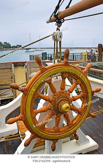 Wooden steering wheel helm aboard The Pilgrim, tall ship docked at Dana Point Harbor, Orange County, California