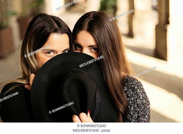 Two best friends hiding their mouths behind black hat