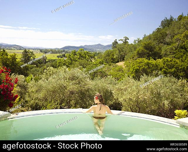 Woman standing with arms outstretched on edge of infinity pool at a luxury resort overlooking wine country in Napa Valley, California