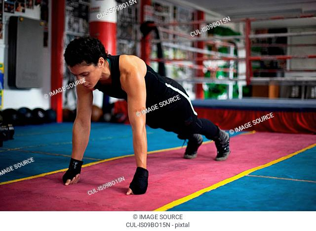 Female boxer doing planks in gym