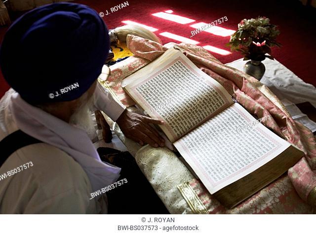 Sikh priest reading scripture, India