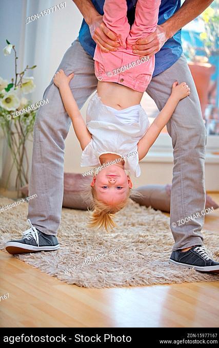 Vater beim Toben mit seiner Tochter zu Hause