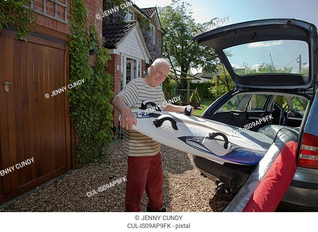 Senior man removing surfboard from car boot