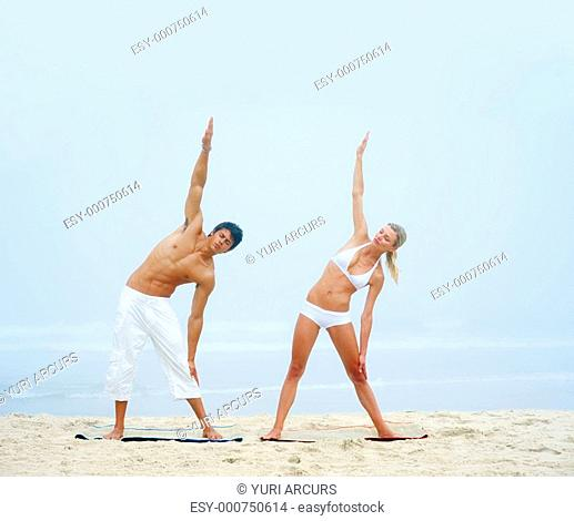 Portrait of a young man and woman working out at the beach together