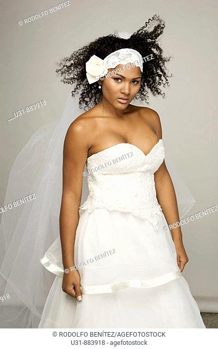 Black Latin Bride in her 20s poses in a studio setting