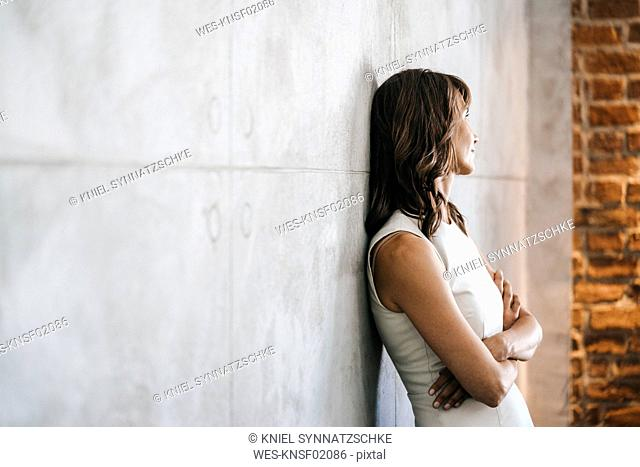Businesswoman leaning against wall with arms crossed