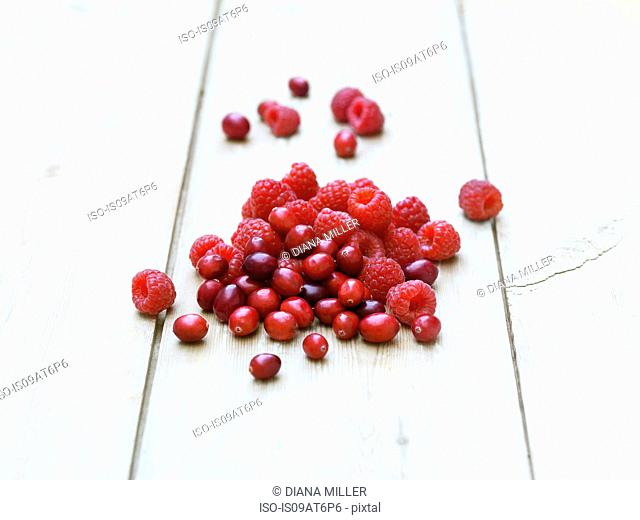 Raspberries and cranberries on whitewashed wooden table