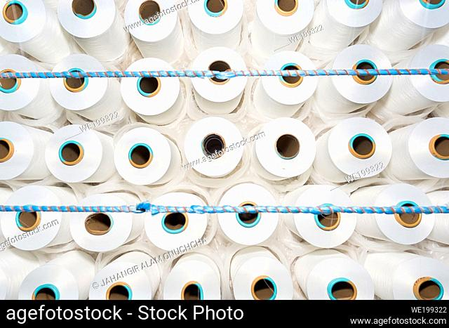 Top view of A lot of white yarn spools in a textile factory. White yarn spools in a clothing factory