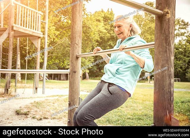 Senior woman during workout on high bar