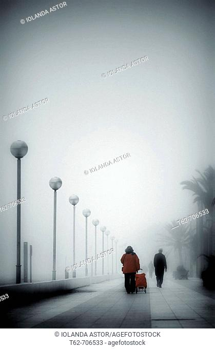 People walking along the promenade in a day of thick fog