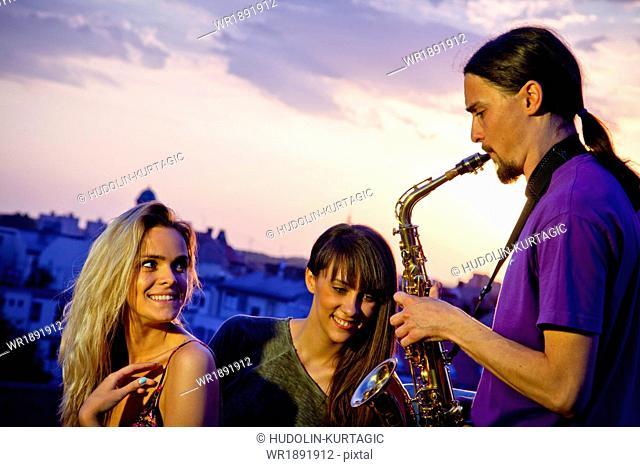 Young man playing the saxophone at sunset, Osijek, Croatia
