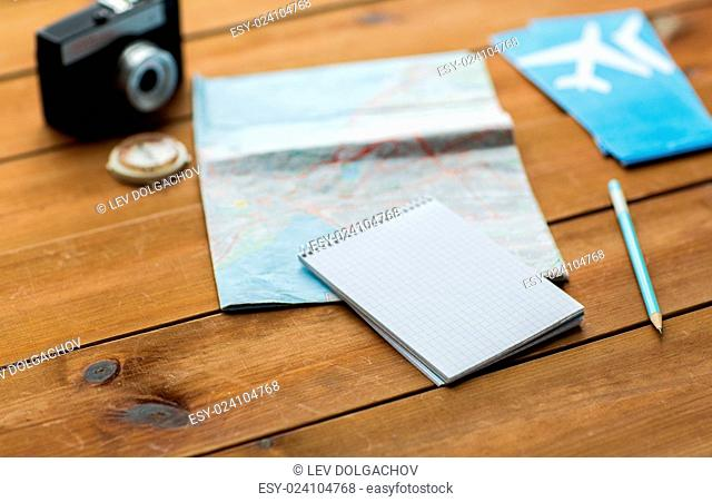 vacation, tourism, travel and objects concept - close up of blank notepad with map and airplane tickets