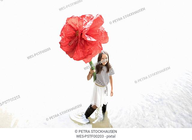 Portrait of smiling girl standing in a lake holding oversized red artificial flower