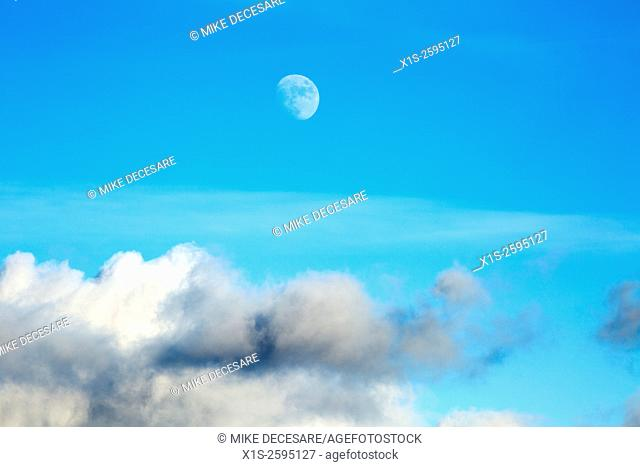 A nearly full moon is visible above a layer of clouds on an otherwise blue sky day