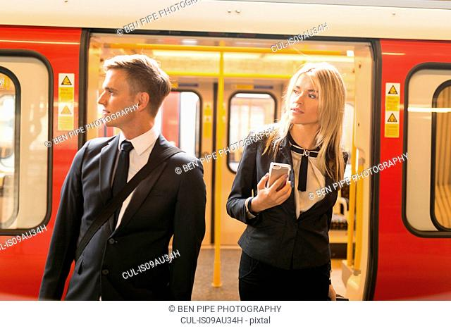 Businessman and businesswoman alighting train, London Underground, UK