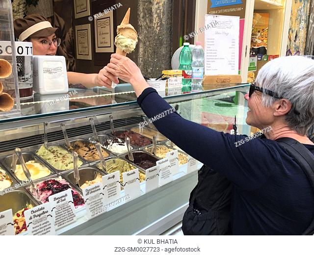 A happy, mature woman, accepts a scrumptious-looking ice cream cone at a stall in the historic part of Naples, Italy