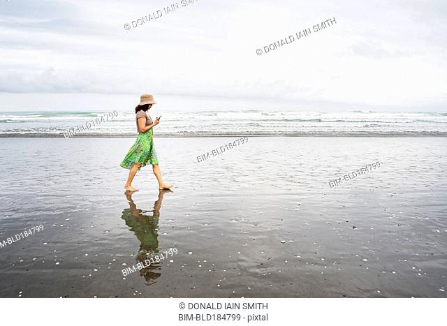 Mixed race woman walking on beach with cell phone