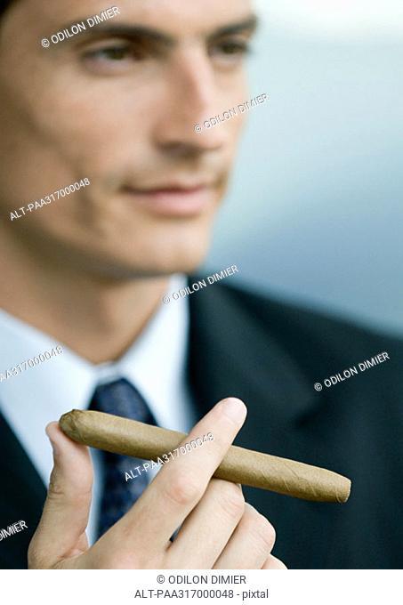 Businessman holding cigar