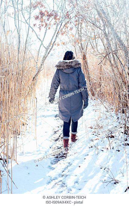 Full length rear view of woman wearing winter coat walking on snowy landscape