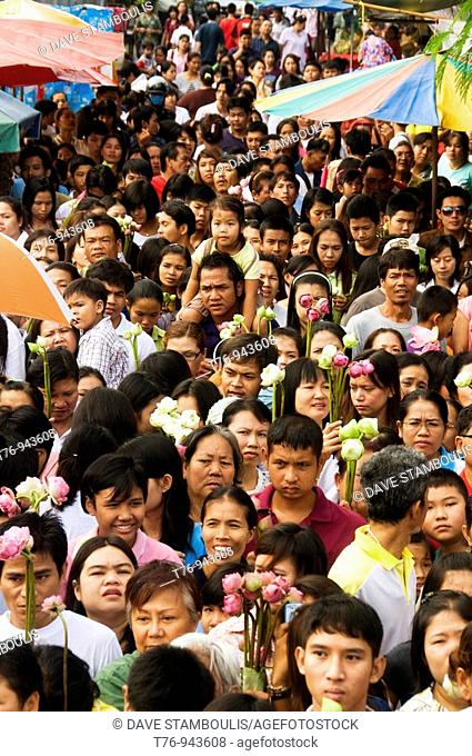 crowd with lotus flowers at the Rap Bua Lotus Throwing Festival in Thailand celebrating the end of Buddhist Lent