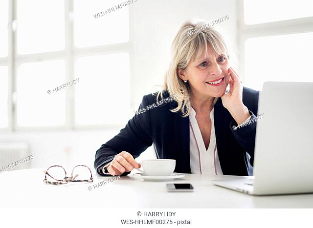 Smiling mature businesswoman with cup of coffee working on laptop at desk in the office