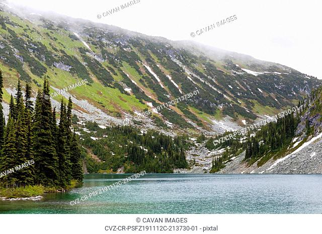 A beautiful alpine lake on a cloudy, rainy summer day in the Coast Mountains around Pemberton, British Columbia