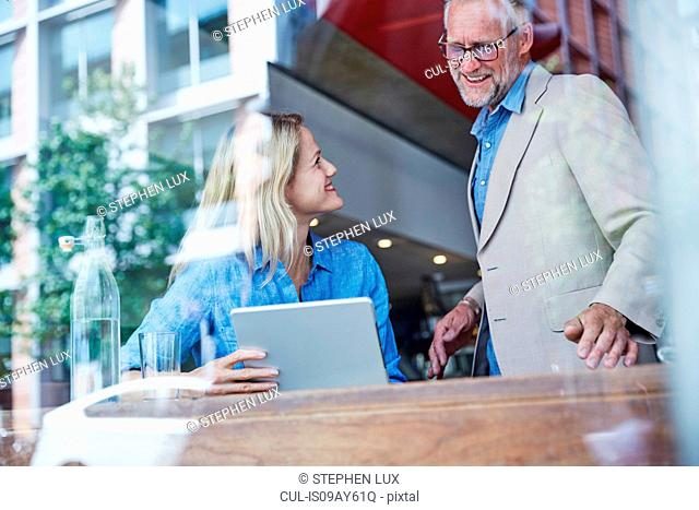 Mature man and woman in cafe, looking at digital tablet