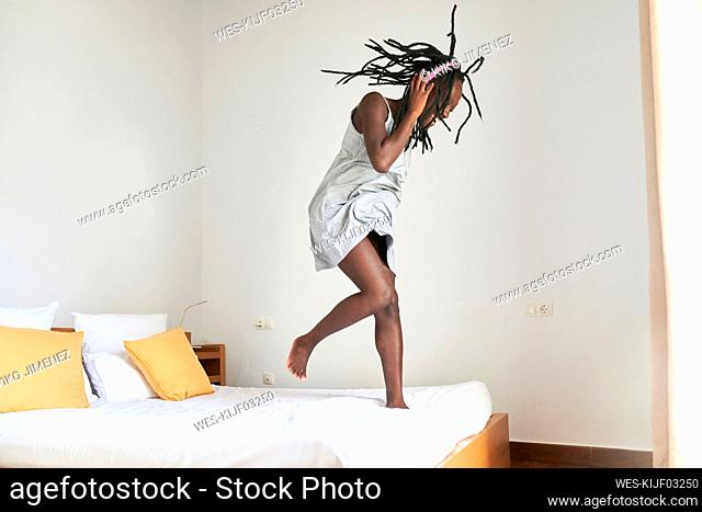 Young woman enjoying dancing and listening music on bed at home