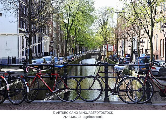 Bycicles on a bridge over a canal. Amsterdam, Netherlands