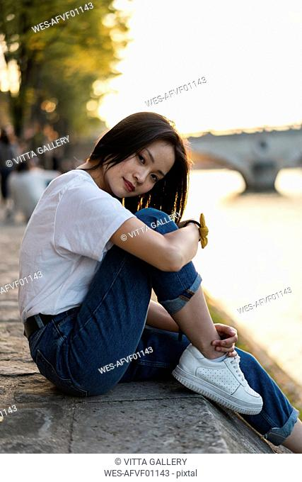 France, Paris, portrait of young woman at river Seine at sunset