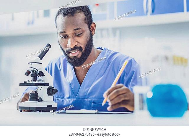 Write report. Young skillful promising biologist wearing blue uniform writing monthly important report