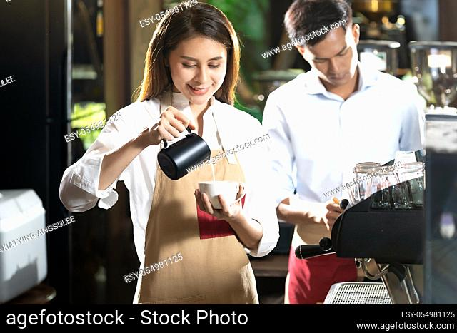 Young adult asian female woman barista pouring fresh milk to prepare latte coffee for customer in cafe bar with her colleague working in background