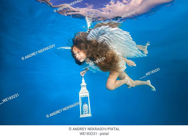 White angel with a flashlight underwater. Underwater girls pictures