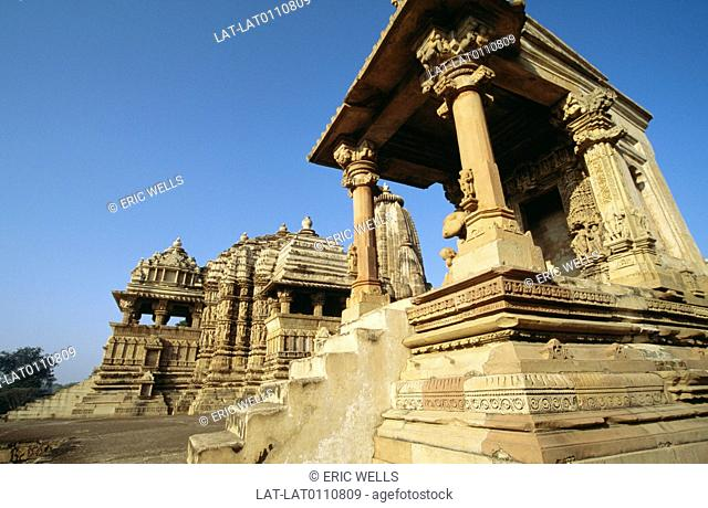 Hindhu temple site. Chandella dynasty. Site famous for erotic carvings. Sandstone pillars,buildings. Carved figures. Khajuraho has a large group of Hindu and...
