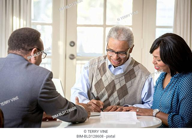 African American father and daughter talking to businessman