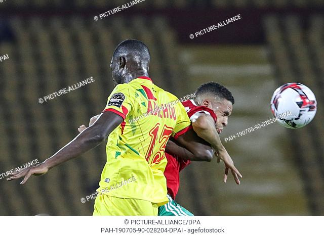 05 July 2019, Egypt, Cairo: Morocco's Youssef En-Nesyri (R) and Benin's Moise Adilehou battle for the ball during the 2019 Africa Cup of Nations round of 16...