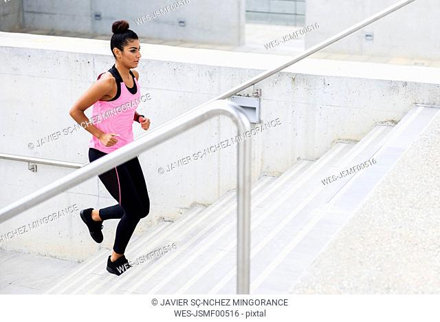 Young woman running up stairs