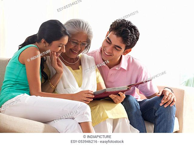 Woman looking at photo album with grandchildren