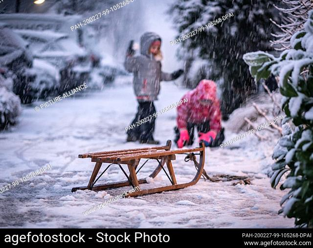 27 February 2020, Hessen, Frankfurt/Main: Behind a sledge, children play on the snowy sidewalk in front of their house in the Bornheim district in the afternoon
