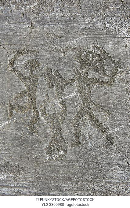 Petroglyph, rock carving, of two warriors fighting, the one on the right has a headress and they both have shields. Carved by the ancient Camunni people in the...