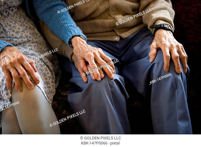 Close-up of senior couple holding hands while sitting