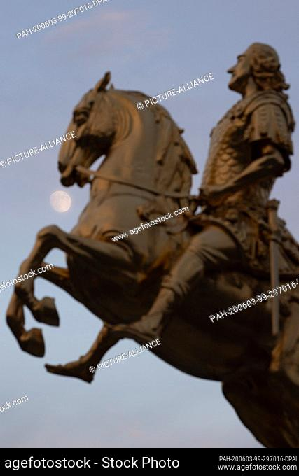 03 June 2020, Saxony, Dresden: The moon rises behind the equestrian statue of August the Strong, the so-called Golden Horseman