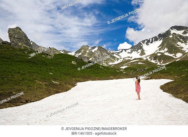 Girl on the glacier enjoying the view of the Pennine Alps, Valais Alps near Great St Bernard Pass, Col du Grand-Saint-Bernard, Colle del Gran San Bernardo
