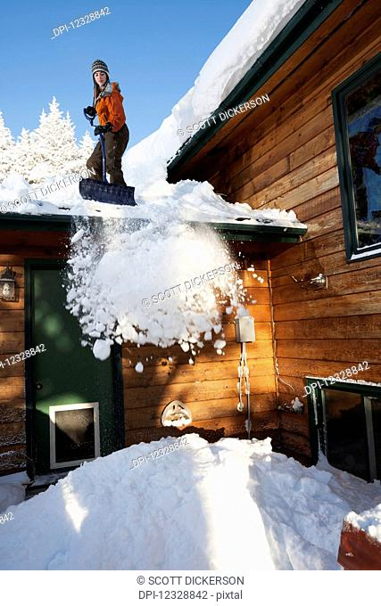 A Young Woman Removes Snow From The Roof Of Her House; Homer, Alaska, United States Of America